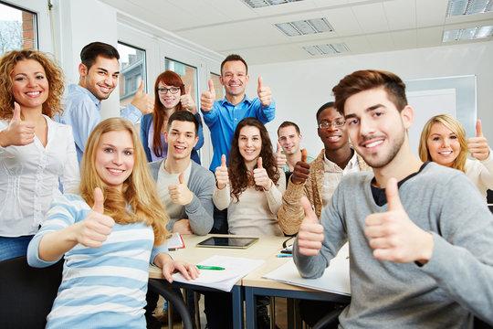 Studenten halten Daumen hoch in der Uni