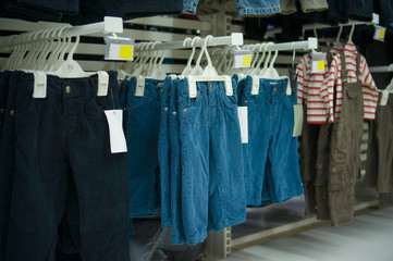 Stand with kids jeans like trousers in supermarket