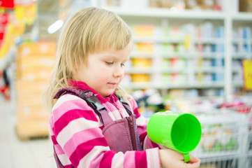 Adorable girl on shopping cart with green cup in supermarket