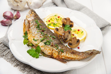Roasted fish with lemon, mushrooms and herbs
