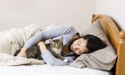 Mature woman holding cat while lying in bed