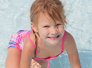 little girl  sitting  in the swimming  pool