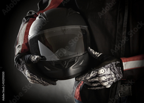 Fototapete Motorcyclist with helmet in his hands. Dark background