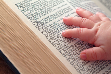 Baby Hand on Open Bible