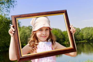 Smiling girl stands outdoors, holding picture frame