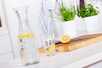 glass and carafe with lemonade on a kitchen counter