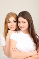 Two girl friends smiling on grey background