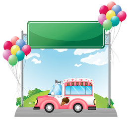 A pink ice cream bus near an empty green board