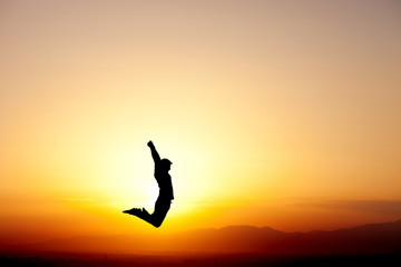 Wall Mural - silhouette of teen jumping in sunset for fun