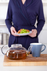 pot of tea and woman holding a healthy breakfast