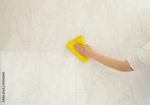 hand cleaning the tiles with yellow cloth
