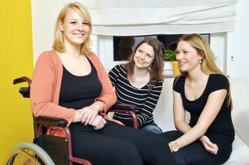 Junge Frau im Rollstuhl mit Freundinnen