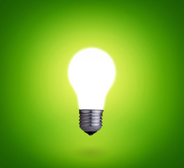 one glowing light bulb on green background