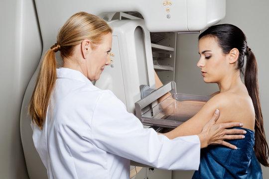 Doctor Assisting Patient Undergoing Mammogram