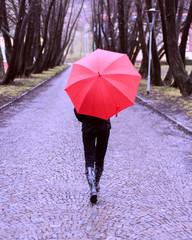 Girl with red umbrella walking away