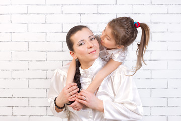 daughter in a white dress kissing his mother