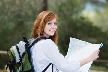 junge frau unterwegs mit rucksack und landkarte
