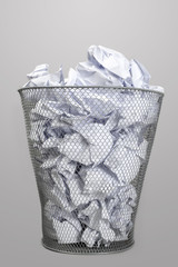 Silver trash bin and papers
