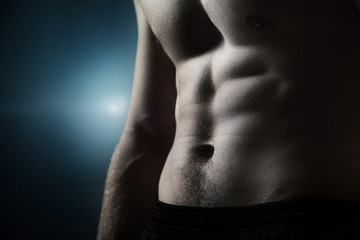 Muscular naked man on dark background