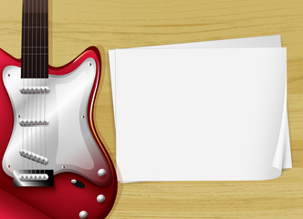 A red guitar with an empty piece of paper