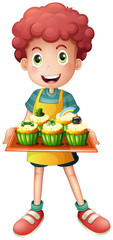 A young baker holding a tray with cupcakes