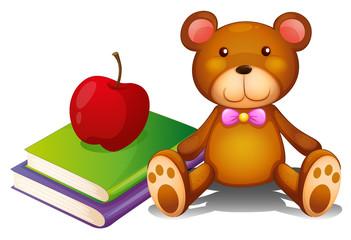 An apple above the books and a huggable bear