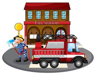A fireman holding a water hose beside a fire truck