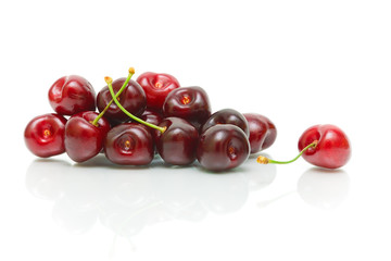 bunch of ripe cherries on a white background with reflection