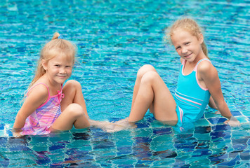 two happy little girls sitting near the pool