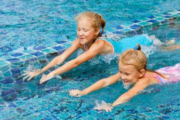 two happy little girls splashing around in the pool