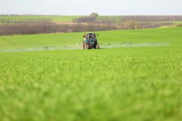 Tractor spraying a green field on a farm