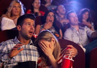 Young couple watching horror in movie theater