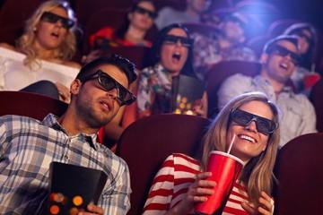 Audience watching 3D film at cinema