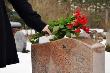 Junge Frau legt Blumen nieder