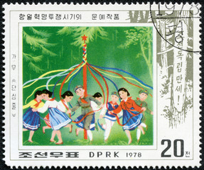 stamp shows people celebrating spring with May Pole