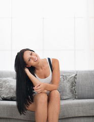 Happy girl sitting on sofa in living room
