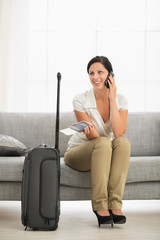 Happy young woman in living room with travel bag talking mobile