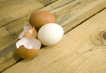dwa jajka i skorupka na drewnianym stole