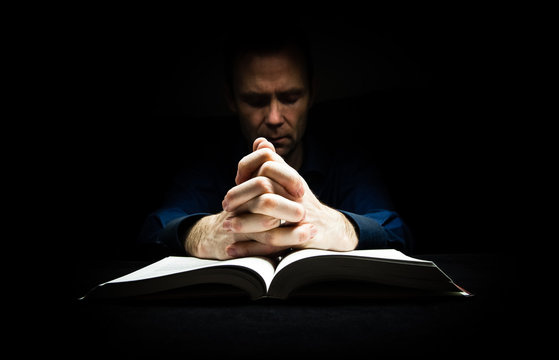 Man praying to God with his hands resting on a bible.