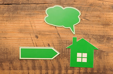 home icon with blank bubble speech and arrow over wooden backgro