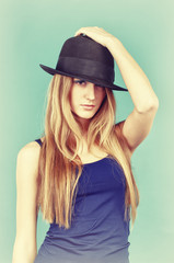 Portrait of beautiful young woman in black hat.
