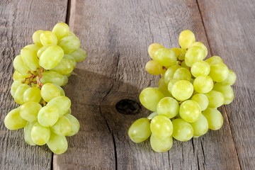 Green organic ripe sweet grapes on a wooden table