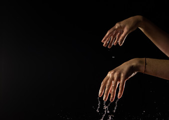 Womens hands moving and dancing with water droplets