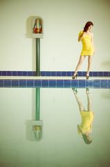 Classy woman in a yellow dress posing in pool