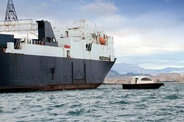 Cargo ship and pilot cutter sailing close to coast