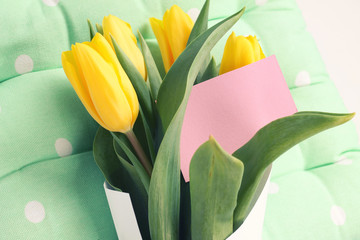 Greeting card and yellow tulips on the blue background