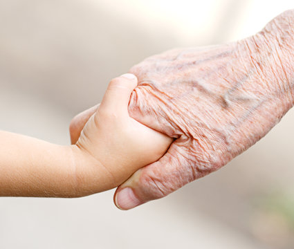An old woman and a kid holding hands together