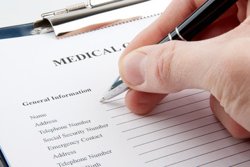 Hand with a pen filling in medical questionnaire form