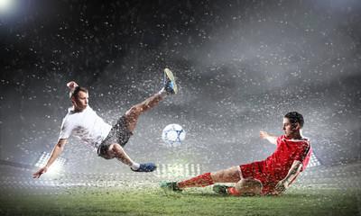 Foto auf AluDibond Fußball two football players striking the ball