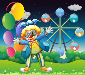 A clown with balloons near the ferris wheel